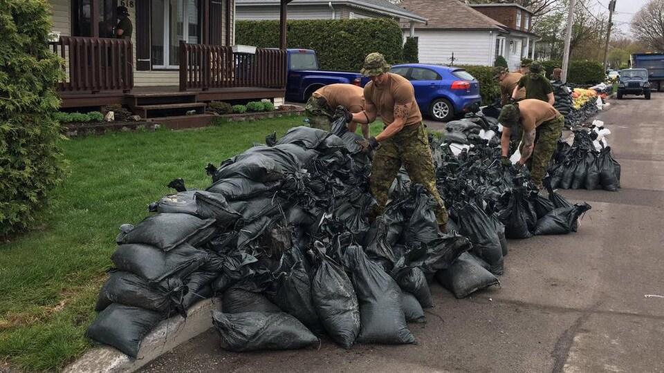 Des militaires ramassent des sacs de sable devant une maison.