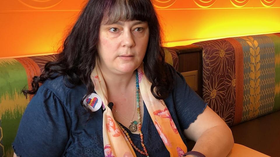 Une femme aux cheveux mauves et aux multiples bijoux fabriqués à la main explique avec ferveur sur les enjeux liés au trouble du spectre de l'autisme dans notre société.