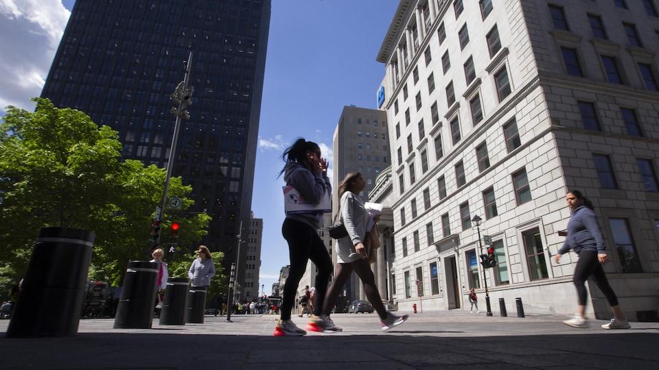 On voit des passants, au premier plan une jeune femme, qui marchent sur la place d'Armes, au centre-ville de Montréal. En arrière-plan, on voit les édifices emblématiques, dont celui de la BMO.
