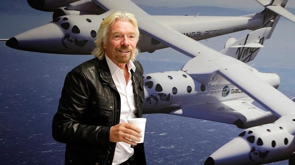 Richard Branson sourit en tenant un verre à la main.