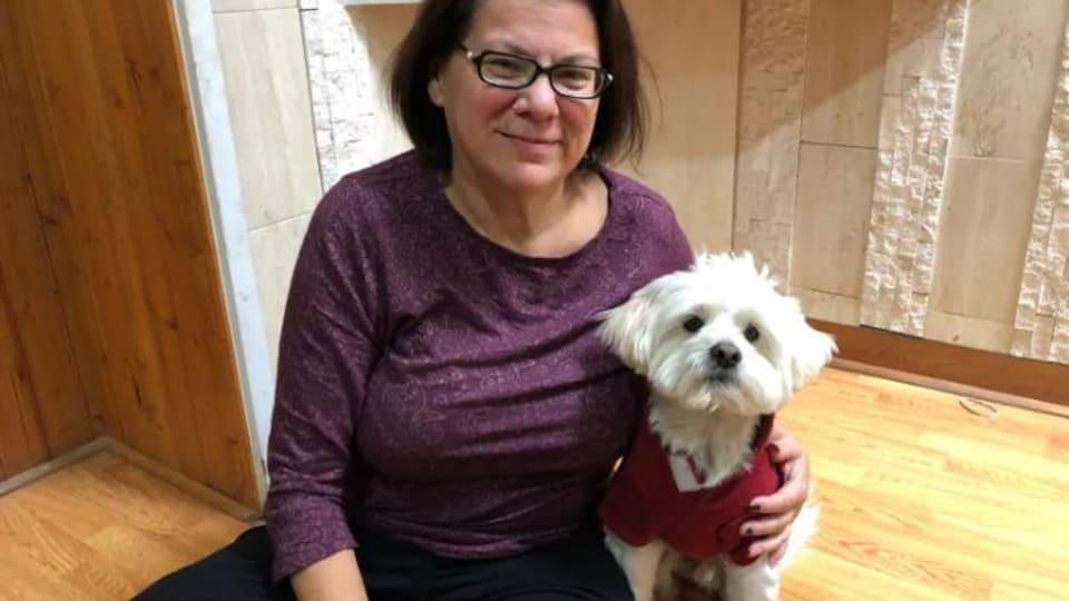 Millie Knapp porte un chandail violet, elle a des lunettes, les cheveux en carré mi-long brun et elle sourit, elle est assise en tailleur et un petit chien blanc qui porte un gilet rouge est à côté d'elle
