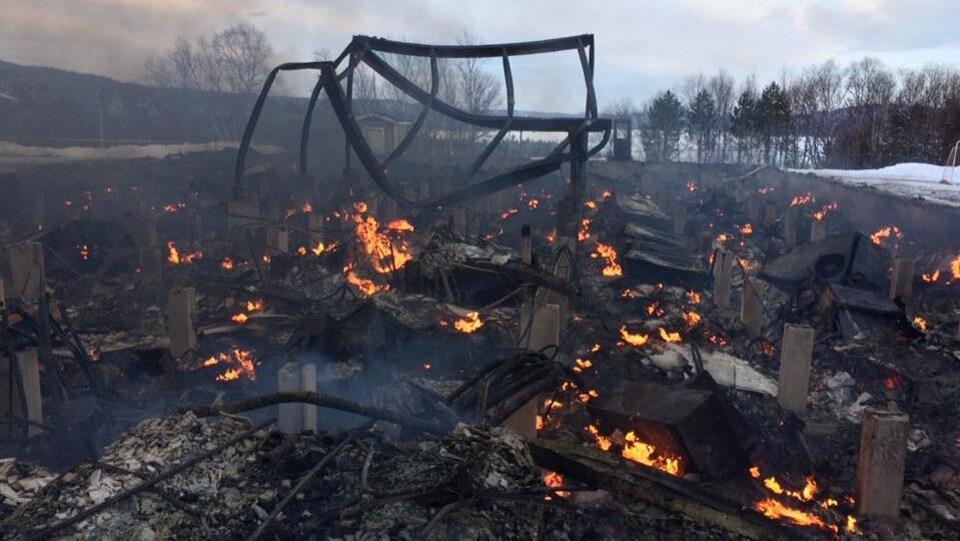 Les restes d'une école brûlent.