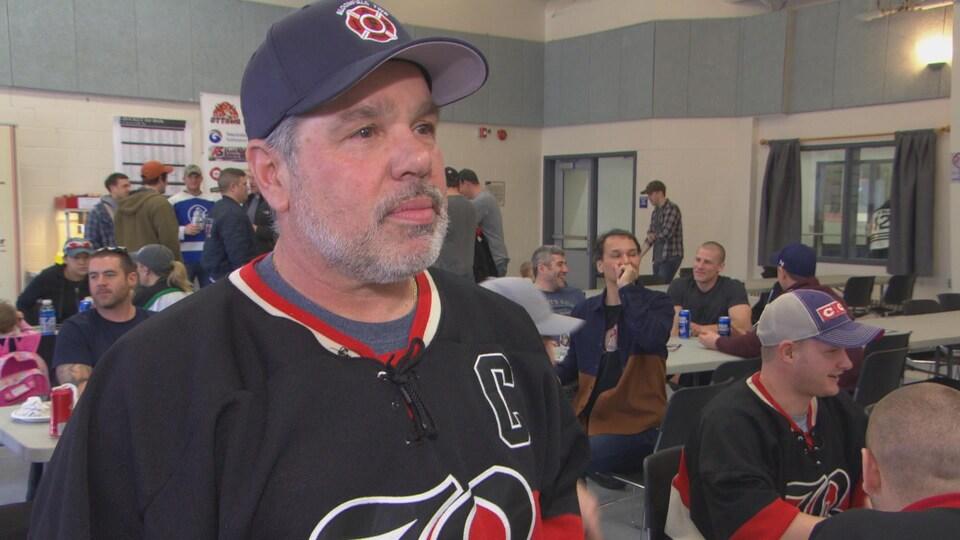 Un homme barbu portant une casquette et un chandail de hockey dans une salle de réception.