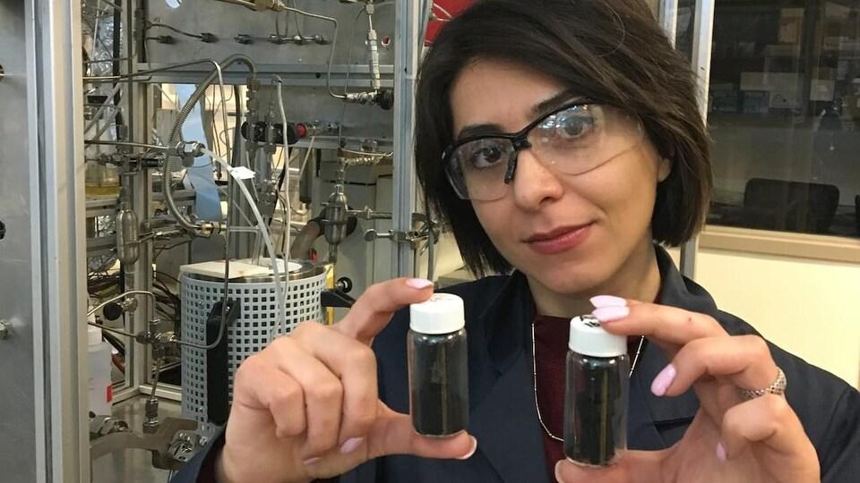 Une femme avec des lunettes de protection tient des tubes en verre remplis de particules noires dans un laboratoire.