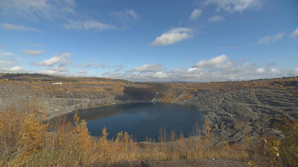 Le fond du gros trou de la mine est rempli d'eau foncée.