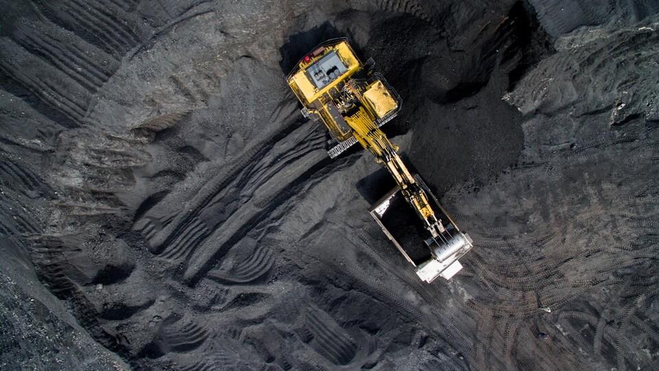 Une pelle mécanique déverse du charbon dans une benne, dans une mine à ciel ouvert, le tout vu du ciel.