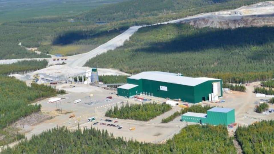 Vue de haut des installations de la mine, entourée par la forêt.
