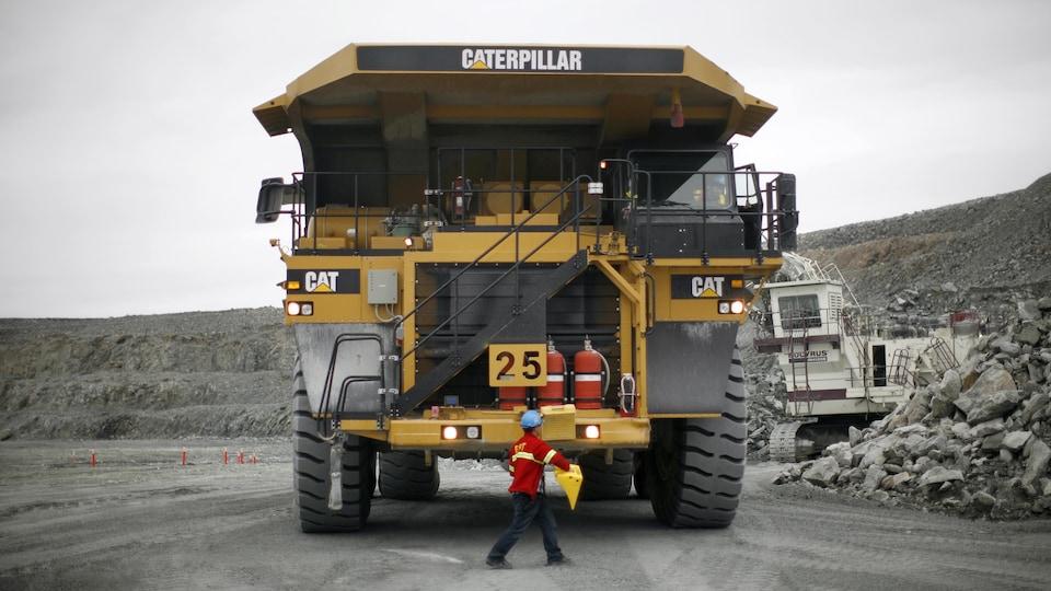 Un travailleur minier marche devant un camion.