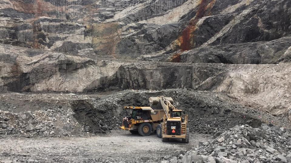 Deux camions charrient des pierres au fond d'un cratère, dans une mine de diamant.