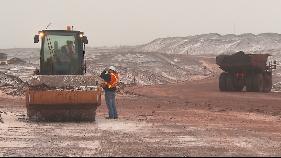 Tracteur et travailleurs sur une mine