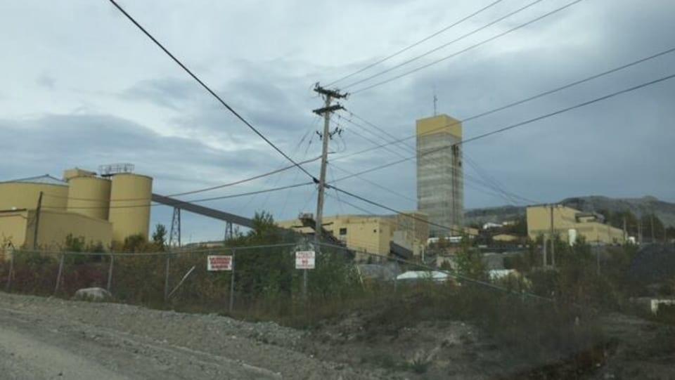 Des bâtiments industriels derrière une clôture.