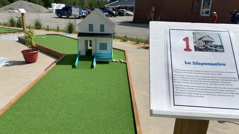 Une petite maison est posée près d'un trou de mini-golf. Une description du Dispensaire qui « permettait l'accès gratuit à certains services médicaux aux colons » est tout près.
