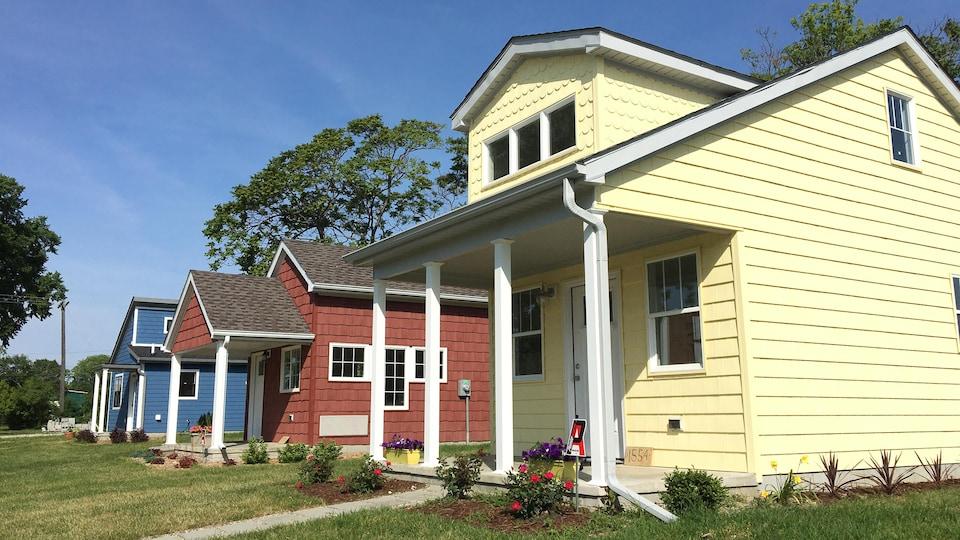On voit trois petites maisons en rangée. Une jaune, une rouge et une bleue.