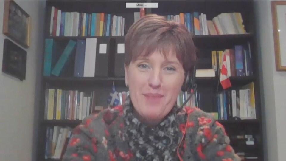Marie-Claude Bibeau parle assise devant une bibliothèque.
