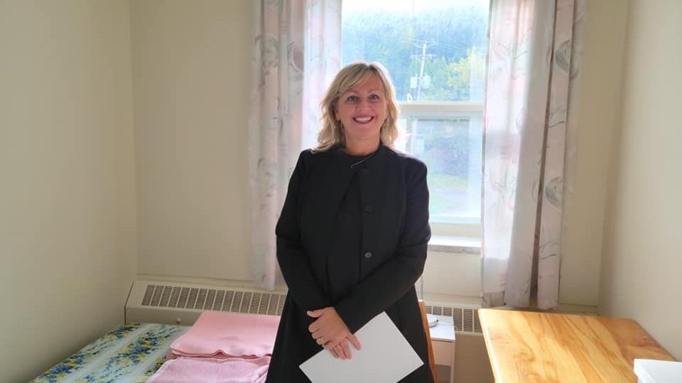 Andrée Laforest sourit dans une petite chambre.