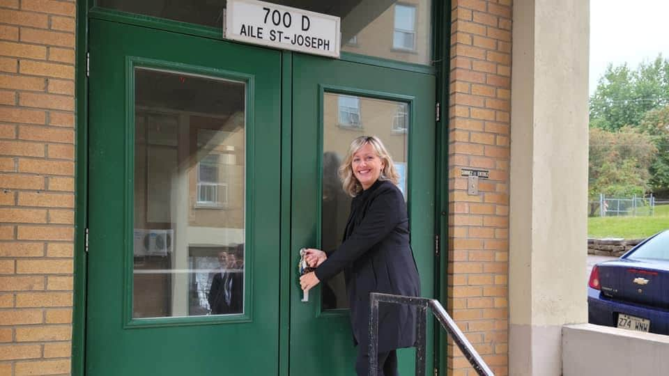Andrée Laforest sourit en tenant une poignée de porte.