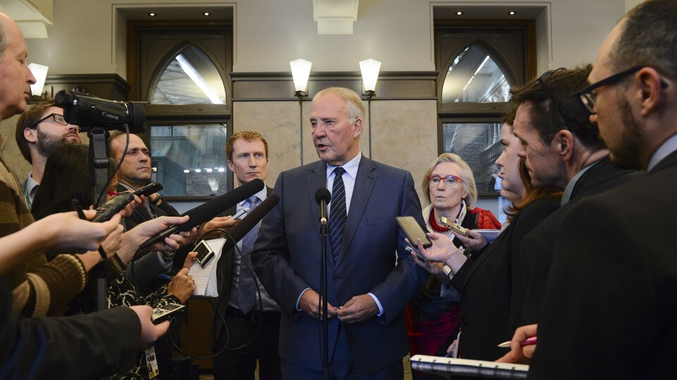 Trois ministres fédéraux, deux hommes et une femme, se tiennent devant des journalistes. Des micros et des caméras sont pointés vers eux.