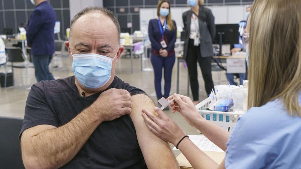 Le ministre, qui porte un masque, se fait vacciner par une femme.
