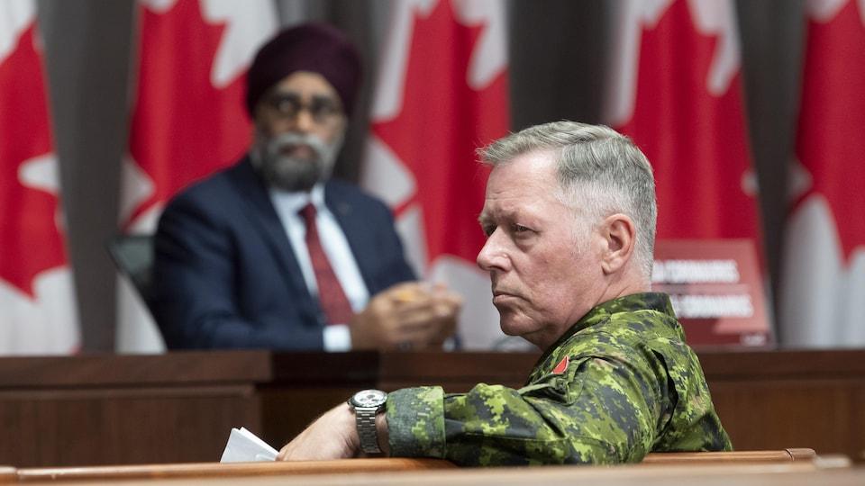 Jonathan Vance, vêtu d'un habit militaire, écoute une question qui lui est posée. Derrière lui, le ministre Sajjan regarde le même interlocuteur.