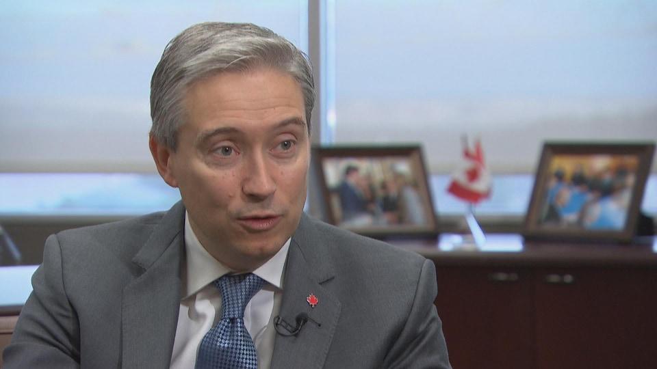 Le ministre des Affaires étrangères François-Philippe Champagne assis à un bureau avec des photos et des petits drapeaux canadiens derrière lui.