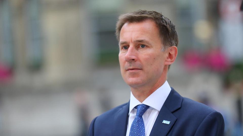 Un homme en veston-cravate regarde droit devant lui en esquissant un léger sourire. Il est photographié de biais et ce qui se trouve derrière lui est flou.