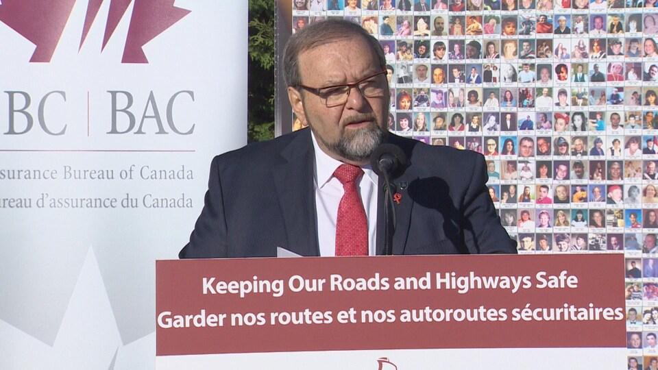 Le ministre Denis Landry devant un micro.