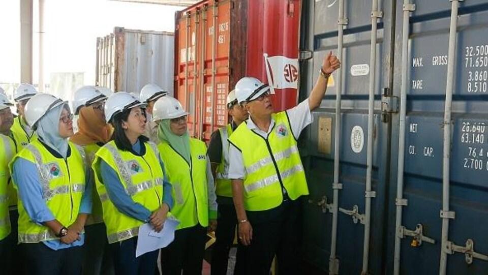 Le ministre malaisien de l'Environnement, Yeo Bee Yin (devant, 2e à gauche), et des fonctionnaires inspectent un conteneur rempli de déchets de plastique le 20 janvier 2020 avant de le renvoyer dans les pays d'origine à Butterworth.