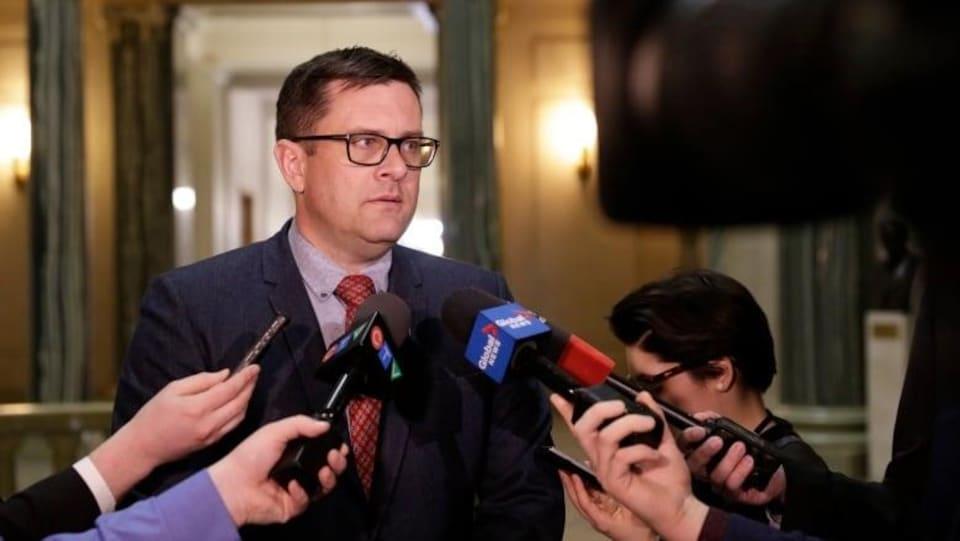 Le ministre Paul Merriman debout donne une entrevue à des journalistes.