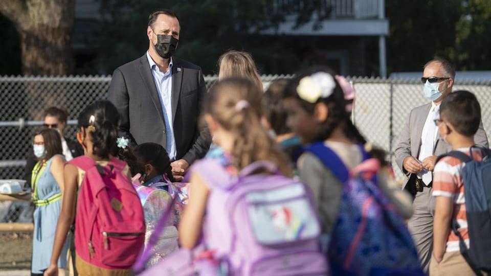 Le ministre de l'Éducation, Jean-François Roberge avec des élèves dans une cour d'école.