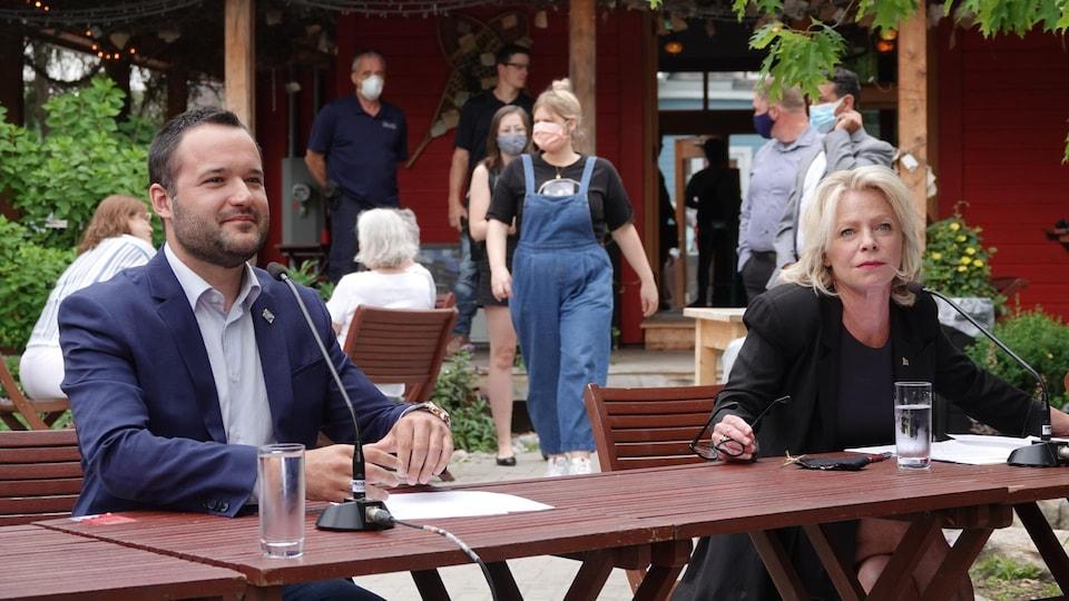 Les deux ministres sont assis à une table à l'extérieur, à deux mètres de distance, prêts pour la conférence de presse.