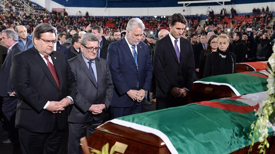 Les maires Denis Coderre et Régis Labeaume et les premiers ministres Philippe Couillard et Justin Trudeau se tiennent les mains et ont la tête baissée, lors des funérailles pour des victimes de l'attentat de Québec.