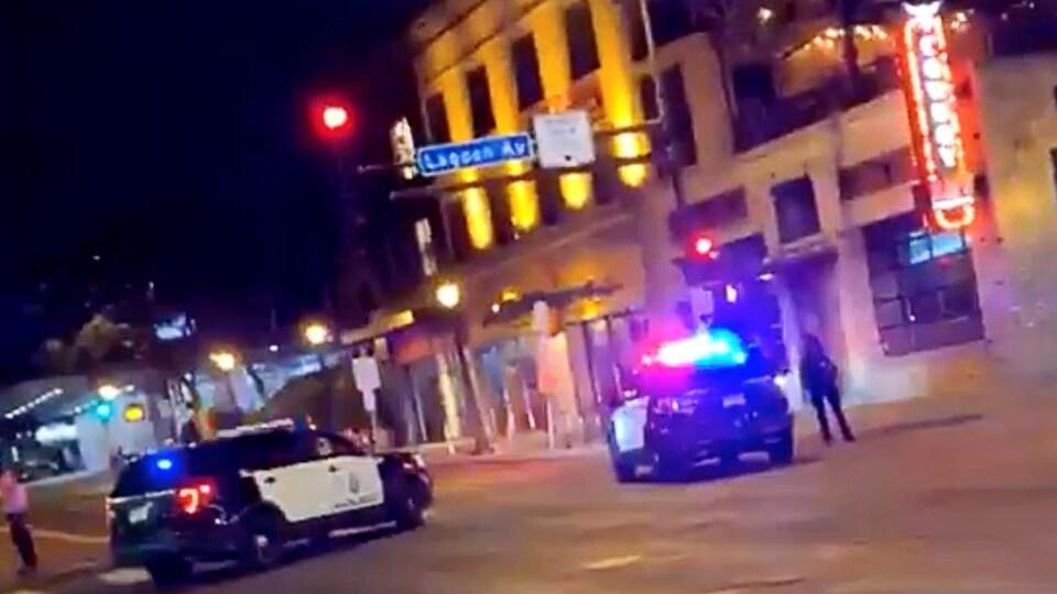 Sur cette capture d'écran d'une vidéo prise d'un cellulaire, deux véhicules de police bloquent la rue.