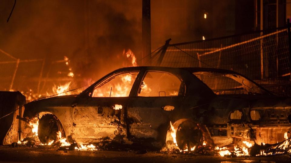 Une voiture brûle.