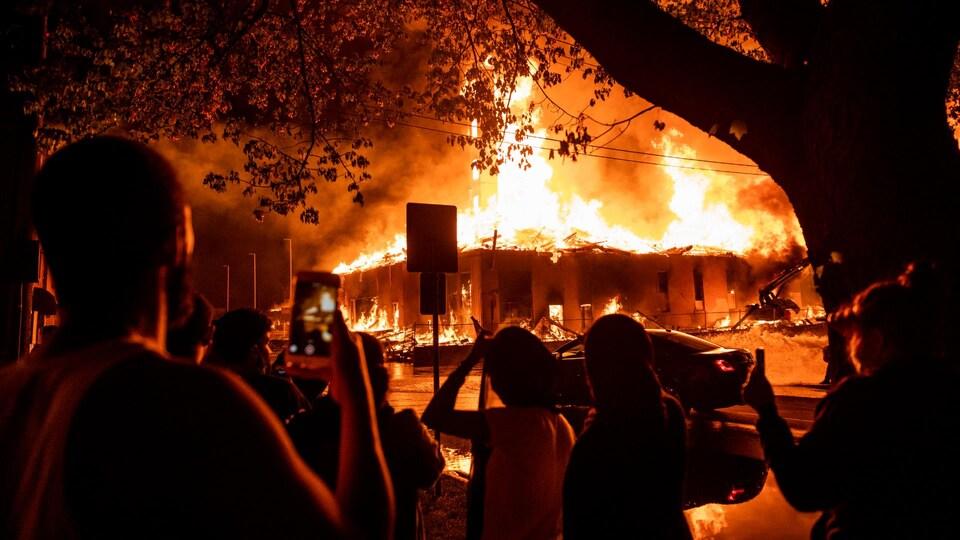 Des curieux regardent un bâtiment en proie aux flammes