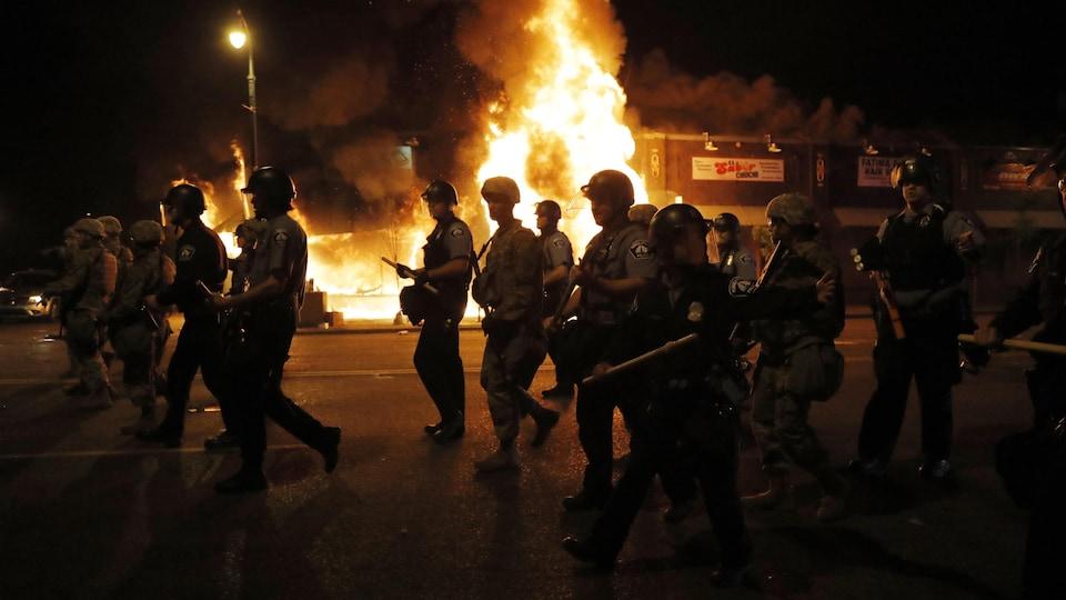 Des policiers dans la rue devant un bâtiment en flammes.