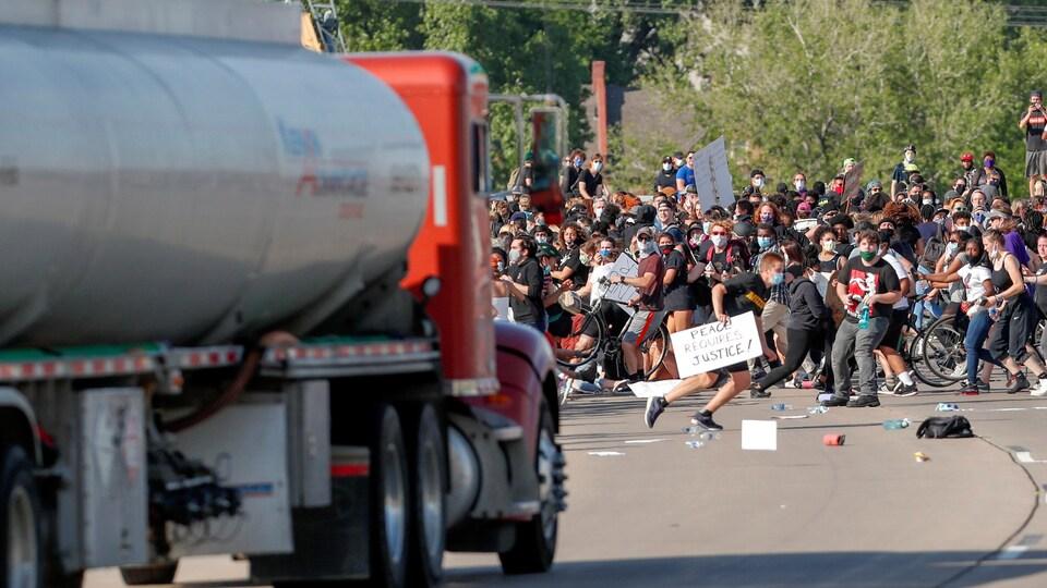 Des gens se tassent du centre de la route à l'approche du camion.