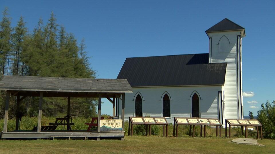 Une église extérieur et une air de repos de tables de pique-nique.  «Minudie Interpretive Park» est écrit sur un écriteau.