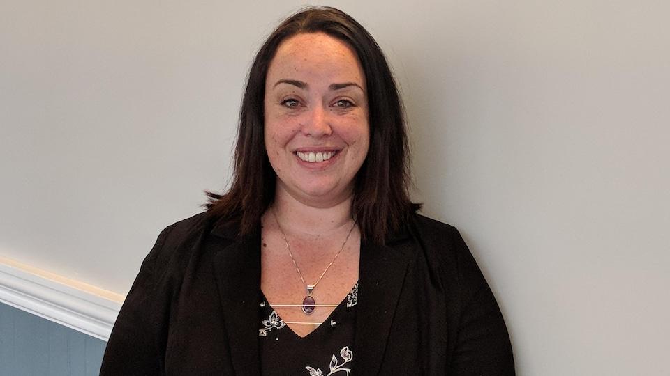 La présidente de l'Ontario Personal Support Workers Association, Miranda Ferrier debout devant un mur.