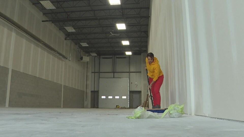 Mireille Tessier passe le balais au milieu de son local vide au sud d'Edmonton.