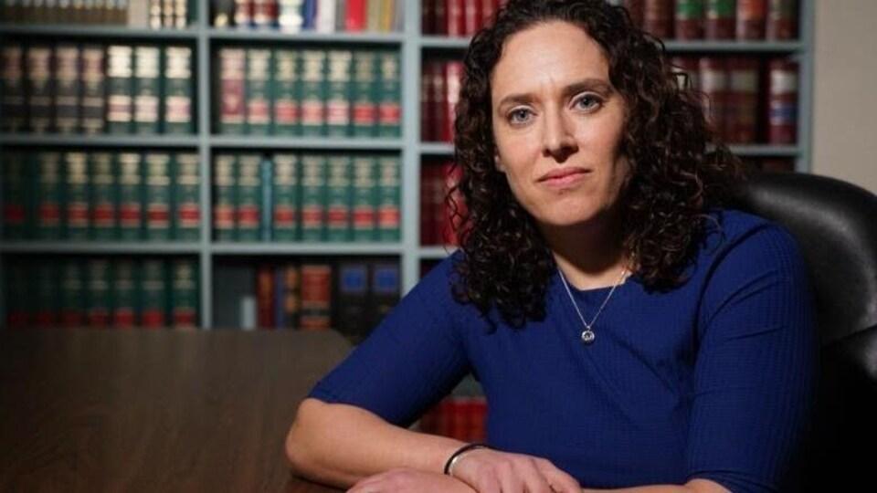 Miriam Vale-Peters assise à une table devant une bibliothèque pose pour la caméra.