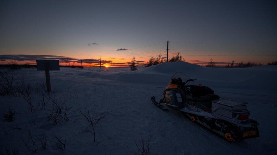 Une motoneige devant un soleil couchant à Miscou, le 2 mars 2021.