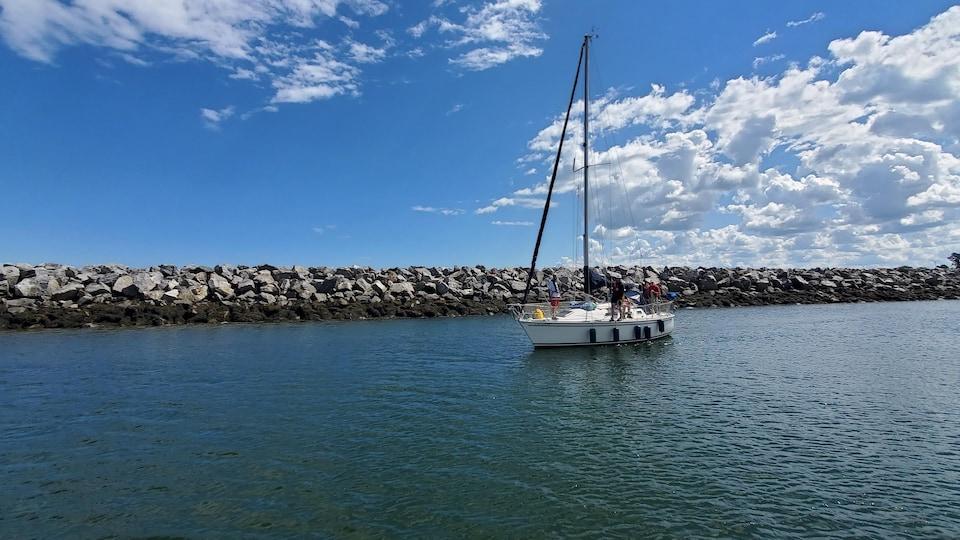 Quatre personnes sont debout sur un voilier au centre d'un bassin à la marina de Rimouski.