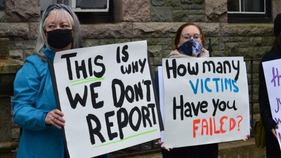 Des femmes manifestent avec des pancartes sur lesquelles sont indiquées ''C'est pour cela que nous ne dénonçons pas''.