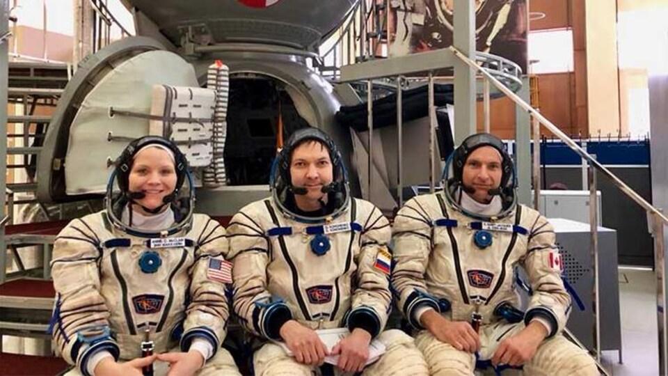 Trois personnes en tenue d'astronaute.