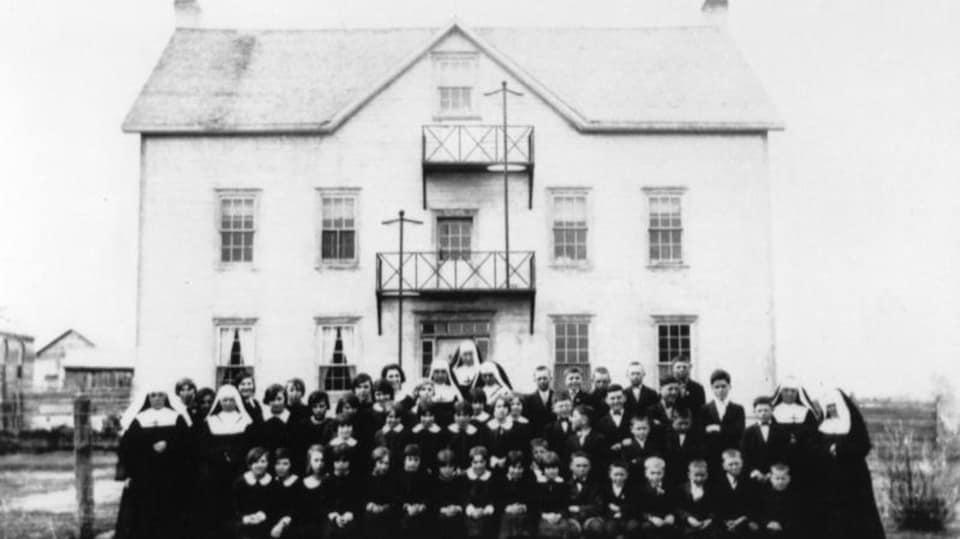 Photo en noir et blanc de religieuses et d'étudiants devant l'édifice du couvent.