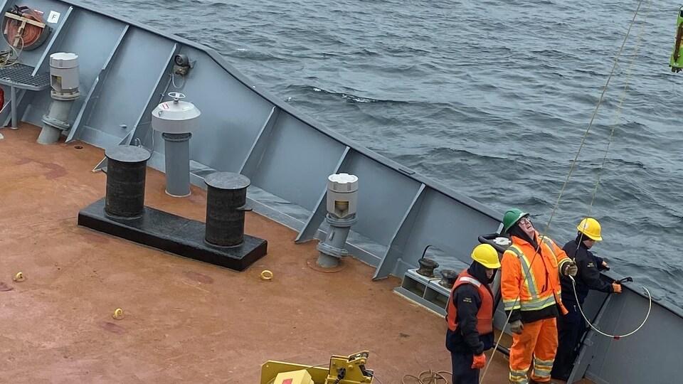 Des hommes sur un bateau en mer qui regardent un objet suspendu.