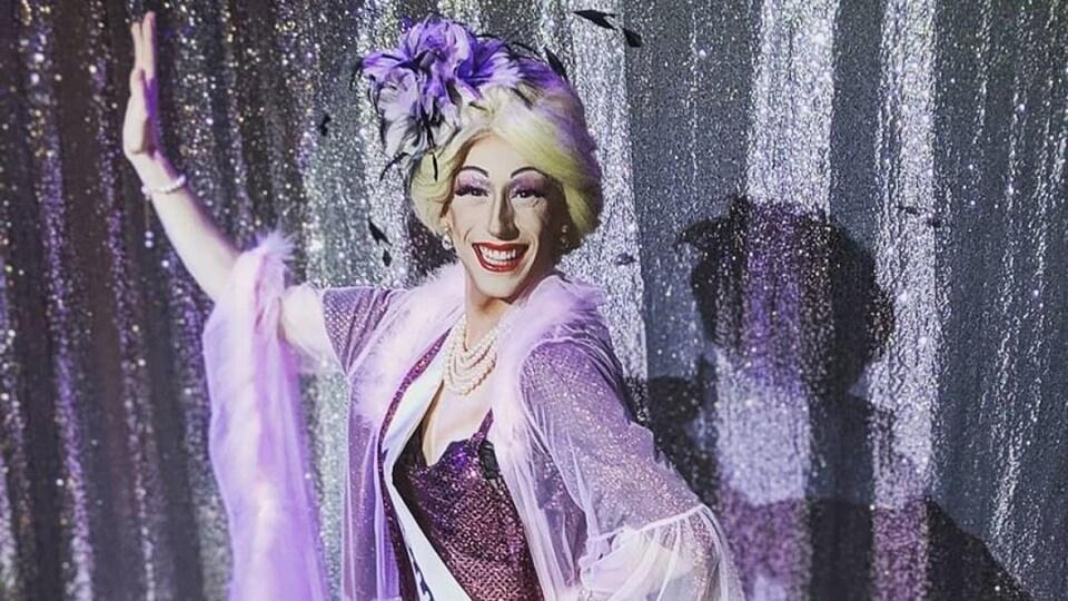 Mitchell Goodine, habillé pour incarner son personnage de drag Amour Love, salue la foule sur une scène et porte une bannière de récompense.