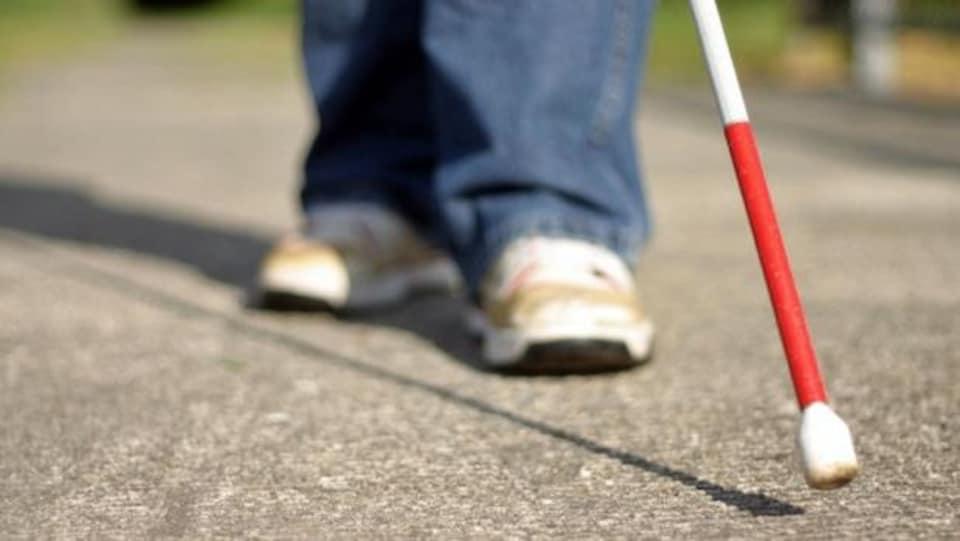 Gros plan sur les pieds d'une personne aveugle munie d'une canne blanche.
