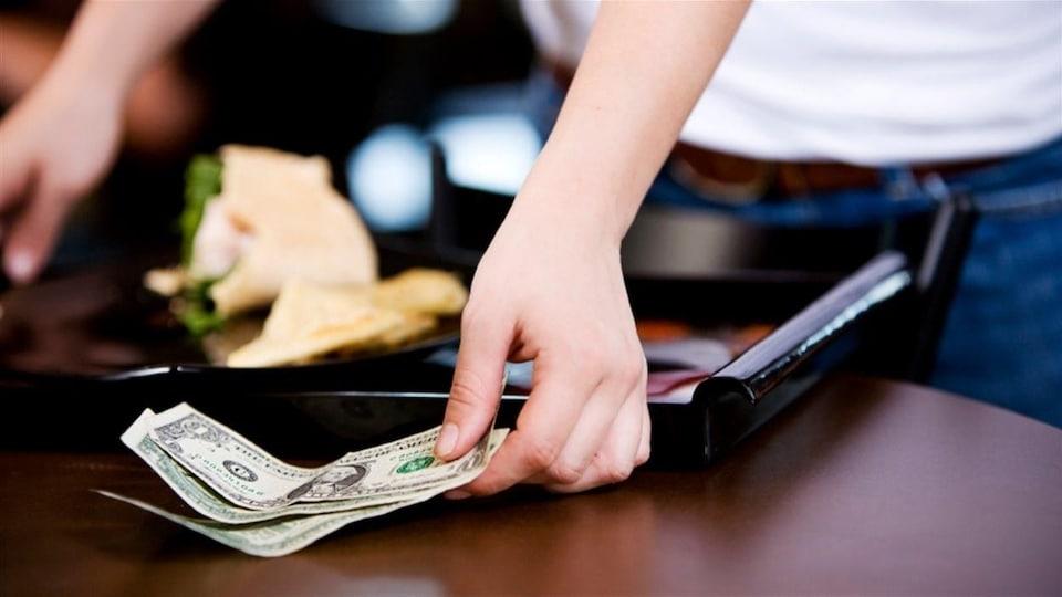 Une serveuse de restaurant récupère un pourboire.
