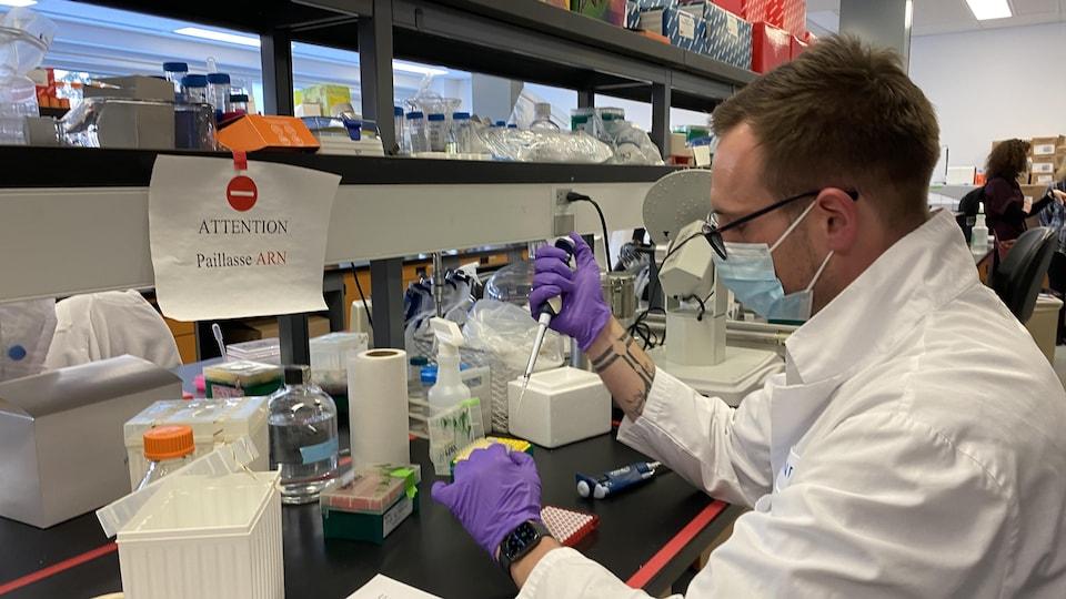 Un homme portant un masque travaillant dans un laboratoire